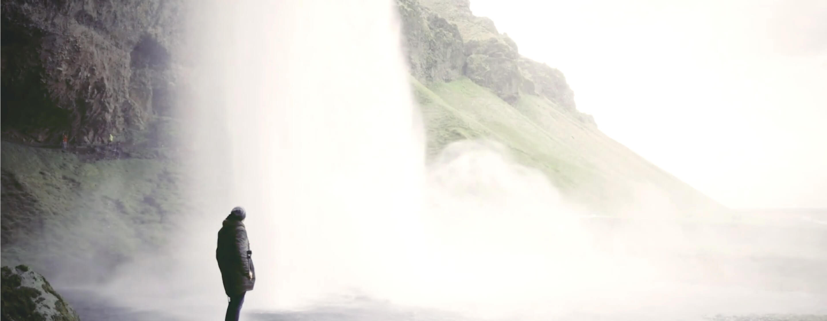 Person in a coat standing next to a massive cascading waterfall with rocks and green hills behind
