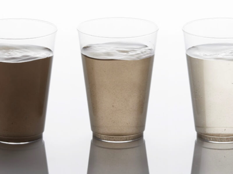 Three glasses containing water of varying degrees of dark cloudiness, showing how AMBERLITE SCAV ion exchange resins can help with total organic carbon or natural organic matter challenges