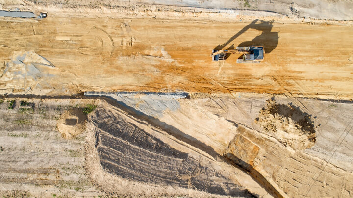 Aerial view of a large piece of excavation equipment on the dusty, scarred surface of a coal mine