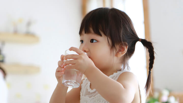 Young girl in a sunny room sips from a glass full of safe and clean drinking water.